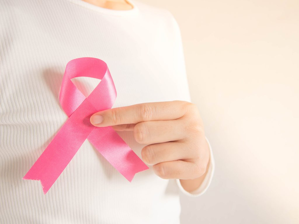 Breast Cancer Awareness Month in October. Closeup of woman in white shirt showing satin pink ribbon awareness for support people who live w/ breast cancer. Health care and medical concept. Copy space.
